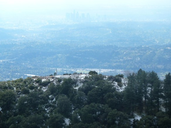 Zoom in view looking down on a lightly snow covered Echo Mountain with Downtown Los Angeles in the background from the Castle Canyon Trail.