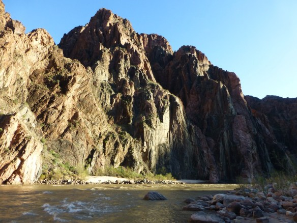 View of the Colorado River with large rock sticking out of it and similar shaped point atop the canyon wall beyond.